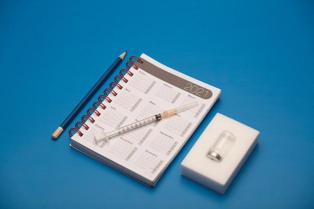 Spritze und impfstoffbehälter, mit kalender 2021, blaue wand
