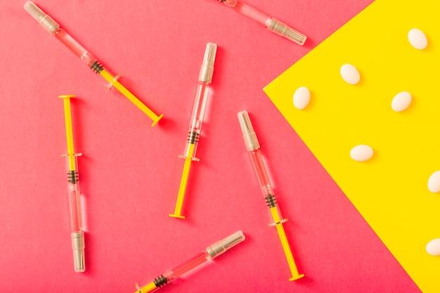 Spritze und weiße pillen über rotem und gelbem hintergrund