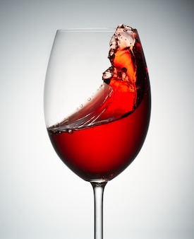 Spritzen bewegt tsunami in einem glas mit rotwein wellenartig. weinkonzept auf steigungsgrau. nahansicht.