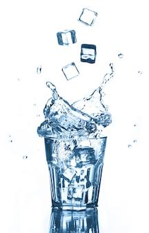 Spritzen des trinkwassers mit fliegeneiswürfeln im glas auf weiß. isoliert.