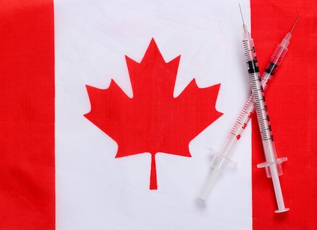 Spritzen mit der flagge kanadas. impfung. pandemie covid-19
