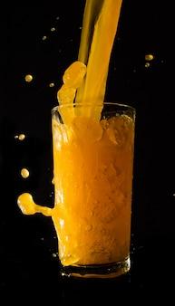 Spritzen orangensaft auf schwarzem hintergrund