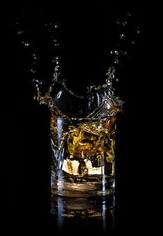 Spritzen sie aus einem eiswürfel in ein glas whisky