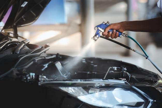 Spritzen sie das motorwachs nach dem waschen des autos ein, damit der motor des autos glitzert und schwarz wird. - wachsen sie den motor.