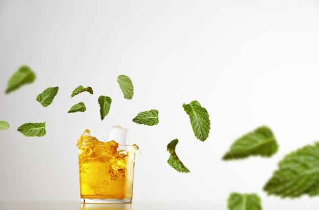 Spritzen sie frische limonade in transparentes glas mit eiswürfeln, die auf weiß isoliert werden