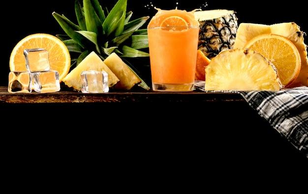 Spritzen sie orangensaft- und ananashintergrund, kopienraum