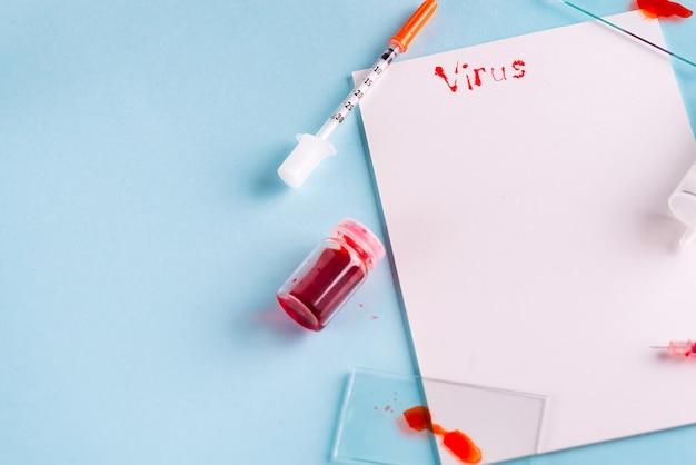 Spritzen und reagenzglas mit blut mit weißbuch und dem aufschrift virus