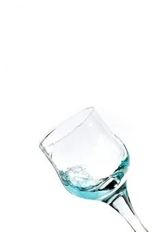 Spritzen von blauem wasser in das glas