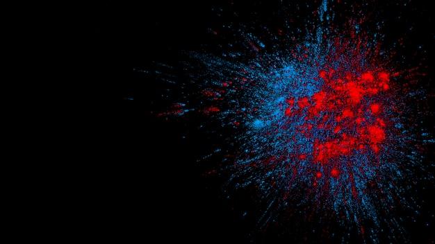 Spritzen von blauen und roten pulverfarben auf schwarzer oberfläche