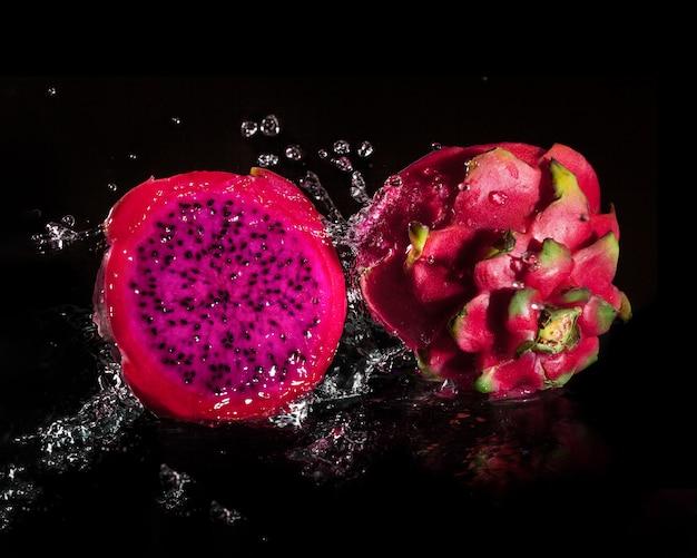 Spritzendes frisches pitaya, das in wasser fällt