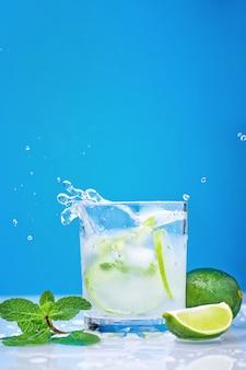Spritzendes mojito cocktail mit kalk und frischer minze im glas auf einem blauen hintergrund