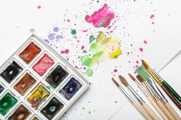 Spritzer aquarellfarbe und malzubehör hautnah