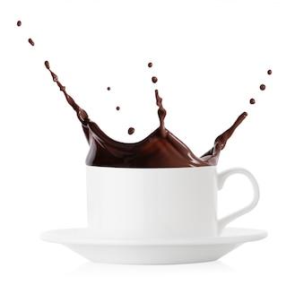 Spritzer heißer schokolade in weiße kaffeetasse und untertasse