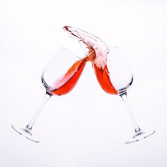Spritzer rotwein aus zwei klarglasgläsern isoliert auf einer weißen oberfläche