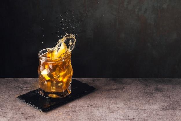 Spritzer tee mit eis und zitrone auf steinoberfläche mit dunklem hintergrund und hochgeschwindigkeitsspritzen