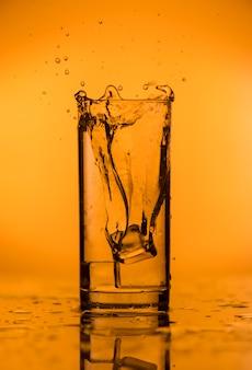 Spritzer von fallendem eis in ein glas mit wasser