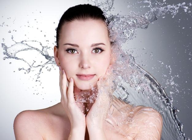 Spritzer wasser auf dem schönen gesicht der jungen frau - grauer raum