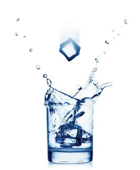Spritzer wasser in einem breiten glas mit fliegendem eis