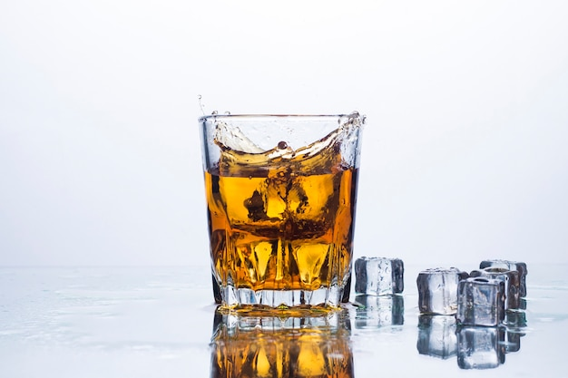 Spritzer whisky aus eiswürfeln. konzept von alkoholischen getränken mit eis, whisky oder weinbrand, apfelsaft und abkühlenden getränken.