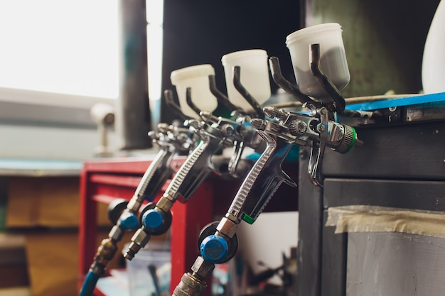 Spritzpistole auf holztisch. im automatischen service. verwendet für industrielle lackierung und beschichtung.