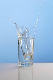 Spritzwasser aus glas isoliert auf weißem hintergrund.