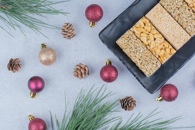 Spröde bonbons auf schwarzem teller mit weihnachtsschmuck.