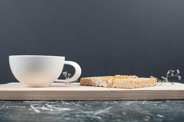 Spröde bonbons und eine tasse tee auf holzbrett. hochwertiges foto