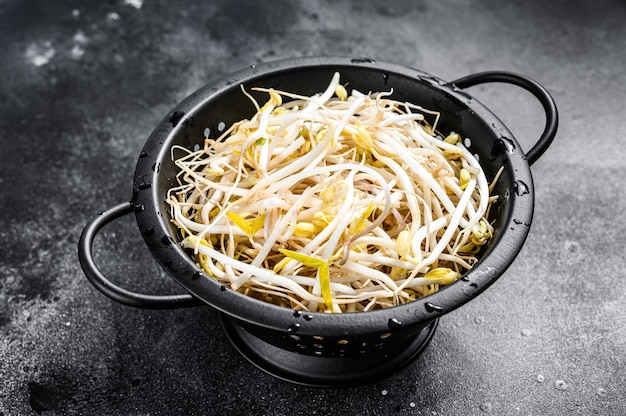 Sprossen von gekeimten bohnen in einem sieb. vegetarisches essen. schwarzer hintergrund. draufsicht.