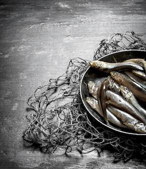 Sprotten in einer schüssel auf dem fischernetz. auf einem schwarzen hölzernen hintergrund.