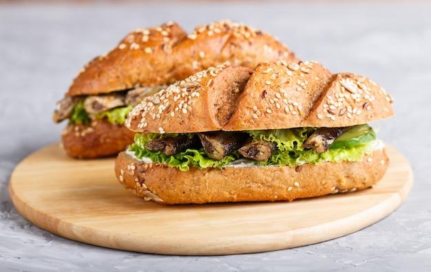 Sprottensandwiche mit kopfsalat und frischkäse auf hölzernem brett auf einem grauen konkreten hintergrund.