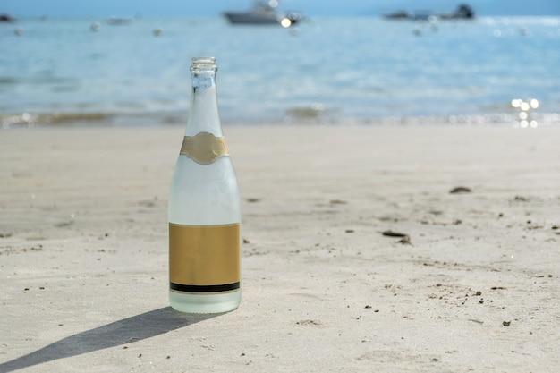 Sprudelnde flasche auf dem strandsand (mit textbereich).