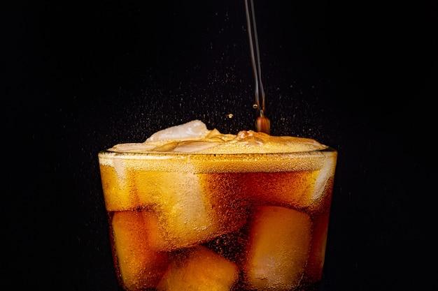 Sprudelndes cola-wasser mit erfrischendem, sprudelndem soda-pop mit eiswürfeln. Premium Fotos