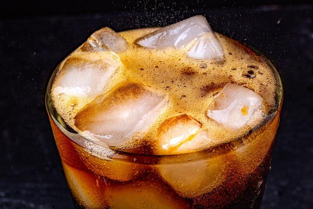 Sprudelndes cola-wasser mit erfrischendem, sprudelndem soda-pop mit eiswürfeln.