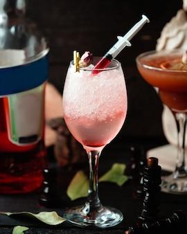 Sprudelndes getränk im glas mit der roten soße geschmückt mit getrocknetem rosafarbenem blumenblatt