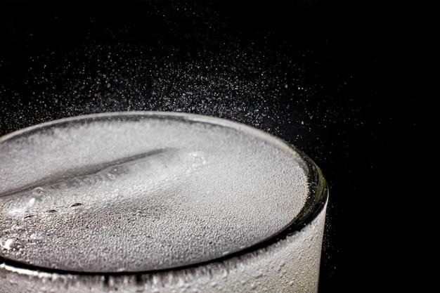 Sprudelndes sprudelwasser erfrischender, sprudelnder soda pop mit eiswürfeln. kaltes erfrischungsgetränk kohlensäurehaltige flüssigkeit frisches und kühles eisgetränk in einem glas. erfrischendes und durstlöschendes konzept.