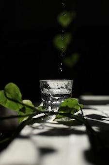Sprudelndes wasser, das in ein glas gegen ein schwarzes gegossen wird