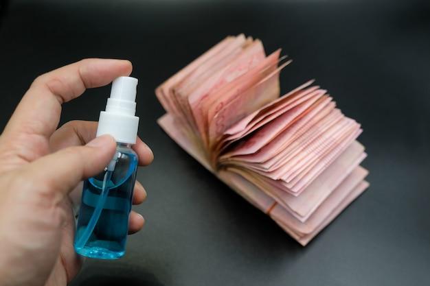 Sprühen sie alkoholgel von hand auf banknoten