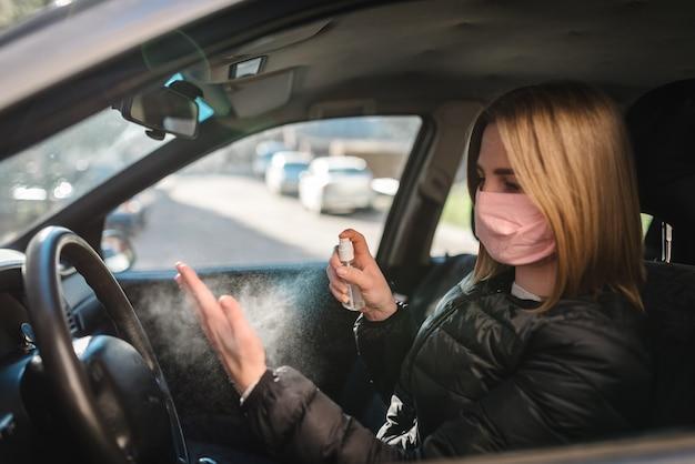 Sprühen von antibakteriellem desinfektionsspray auf hand im auto, infektionskontrollkonzept. desinfektionsmittel gegen coronavirus, covid-19, grippe. sprühflasche. frau, die in der medizinischen schutzmaske ein auto fährt.