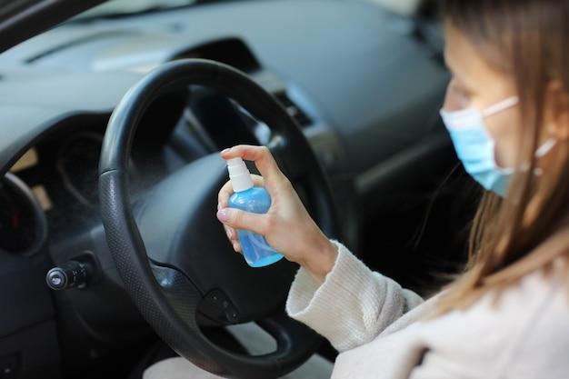 Sprühen von antibakteriellem desinfektionsspray zur hand im auto, infektionskontrollkonzept. desinfektionsmittel gegen coronavirus, covid-19. sprühflasche. frau, die in der medizinischen schutzmaske ein auto fährt.