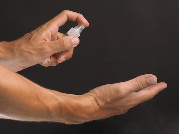Sprühen von männlichem handalkohol aus einer kleinen flasche, um die ausbreitung von keimen, bakterien und viren zu verhindern. händedesinfektionsmittel.