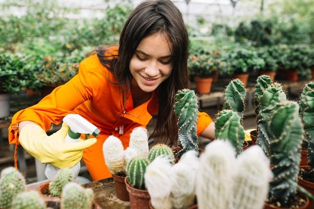 Sprühwasser des glücklichen weiblichen gärtners auf saftigen anlagen