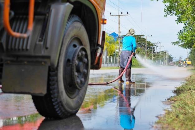 Sprühwasser einer arbeitskraft, zum der straße mit druckwassersystem, nassreinigung der straße zu säubern.