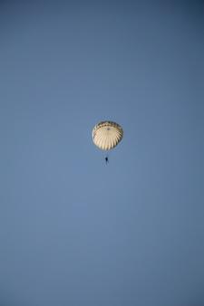 Sprung des fallschirmjägers mit weißem fallschirm, militärfallschirmpullover im himmel.