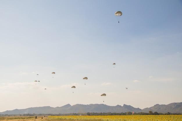 Sprung des fallschirmjägers mit weißem fallschirm