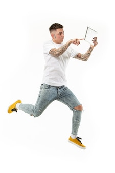 Sprung des jungen mannes über weißen studiohintergrund unter verwendung des laptop-computers während des springens.