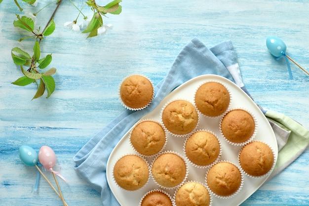 Sptingtime flach lag mit muffins, ostereiern und apfelblüten auf hellblauer oberfläche