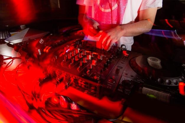Spühr die musik! schnitt von dj, der sich in der nähe der verschwommenen konsole aufhält. live-set im nachtclub. verrücktes partykonzept. helle rote lichter im vordergrund. raving die ganze nacht lang.