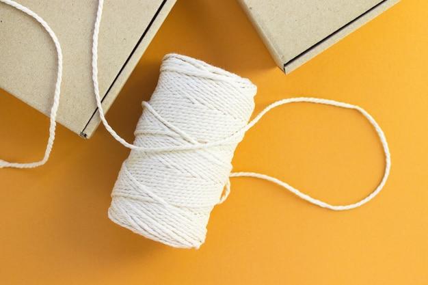 Spule aus baumwollseil und kartons. umweltfreundliche verpackung, paket. plastikfrei, recyceln. sichere lieferung, online-shopping. ansicht von oben, flach, orangefarbener hintergrund.