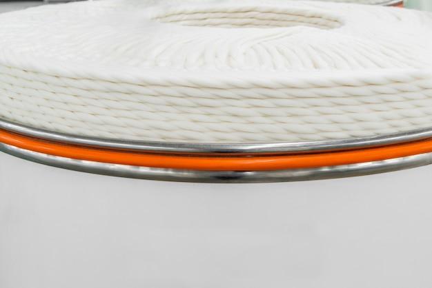 Spule aus dickem weißem faden in einem metalltank. nahaufnahme