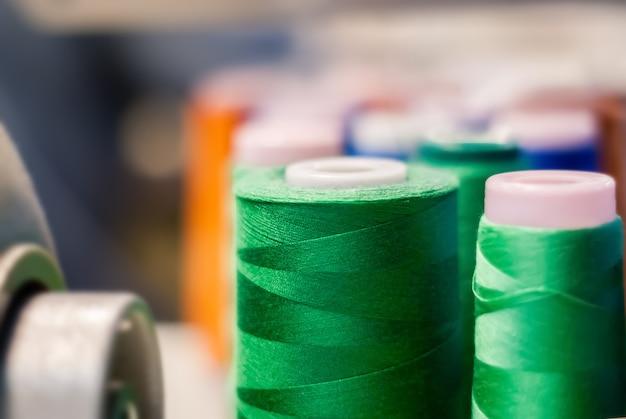 Spule aus grünem faden in der bekleidungsindustrie auf unscharfem hintergrund